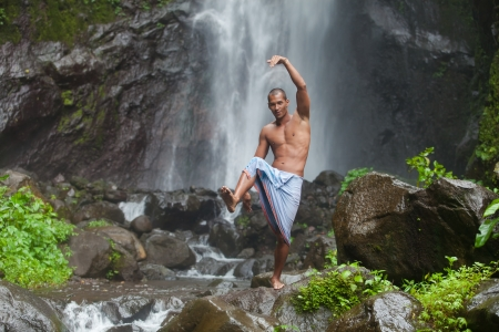 Young handsome man enjoying waterfall in the tropics photo