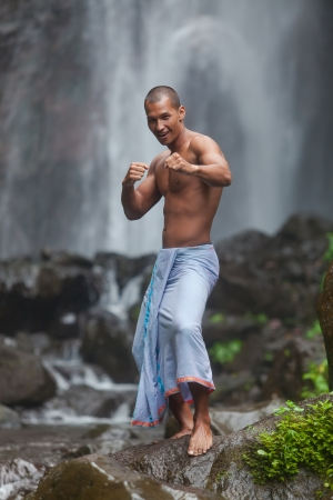 Young handsome man enjoying waterfall in the tropics photo