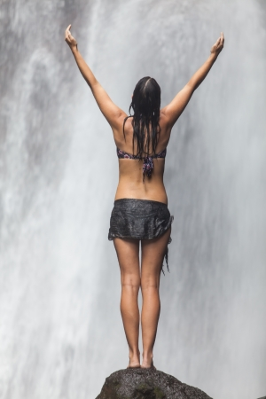 yoga rocks: Young beautiful caucasian woman enjoying waterfall in the tropics
