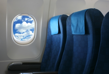 Airplane seat and window inside an aircraft with view on sea