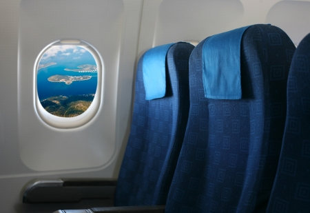 Airplane seat and window inside an aircraft with view on sea photo