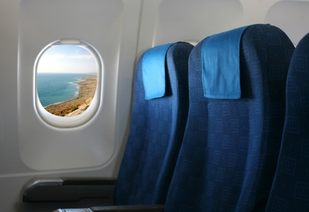 Airplane seat and window inside an aircraft with view of coast over the dead sea in israel