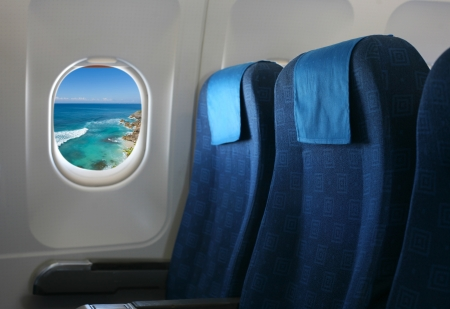 Airplane seat and window inside an aircraft with view on sea and coast in Uluwatu in Bali  Stock Photo