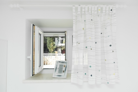Open window with white curtain half drawn photo