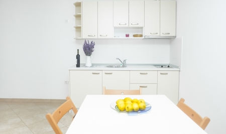 Modern and bright kitchen area in house interior with lemons on table Standard-Bild
