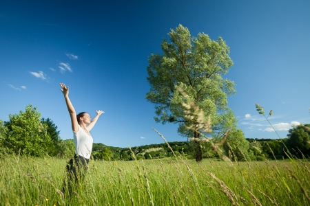 Young beautifull woman relaxing with arms raised in nature with tree in background and grass in foreground  Stok Fotoğraf