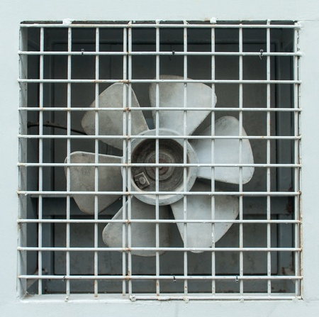 Extractor fan propellers behind metal grid photo