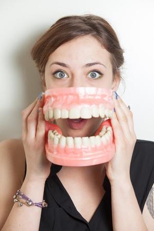 false teeth: Pretty young woman  with oversized false teeth denture