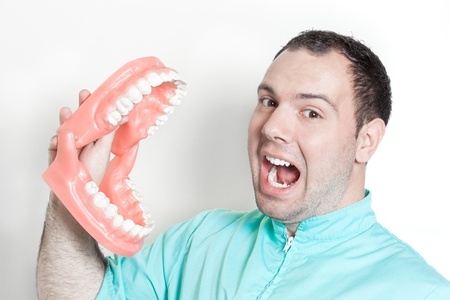 Dentist holding oversized false teeth dentures photo