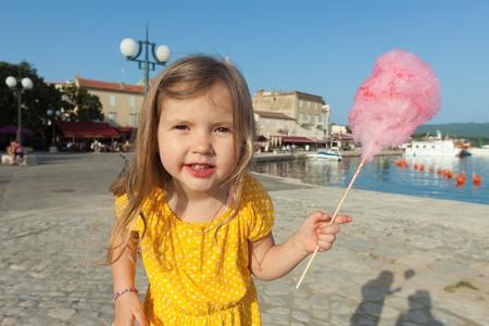 algodon de azucar: Niña bonita que come la seda del caramelo