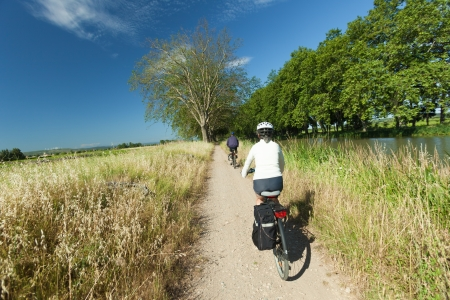 on the canal: Woman and man cycling on path near river on the canal du midi in France.