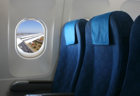 Airplane seat and window inside an aircraft photo
