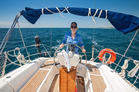deportes nauticos: Joven mujer de pie en el tim�n de un barco contra un cielo azul