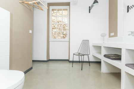 Big comfortable toilet room with chair and towel shelves.