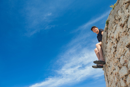 Young man sitting on the edge of stone wall and smiling to the camera. Stock Photo - 27467377