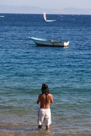 dahab: Man entering the warm waters of the red sea in Dahab, Egypt