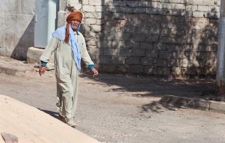 dishdasha: DAHAB, EGYPT - FEBRUARY 2, 2011: Man in traditional dresses walking on February 2, 2011 in Dahab, Egypt. Dishdasha is an ankle-length garment, usually with long sleeves, similar to a robe. Editorial
