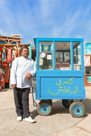 cheapest: DAHAB, EGYPT - JANUARY 29, 2011: Vendor on the street next to stand on January 28, 2011 in Dahab, Egypt. Street food is the cheapest way for tourists to get a meal.