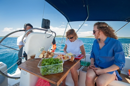 sallad: Women preparing a meal on a boat on a sunny summer day.