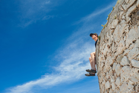 Young man sitting on the edge of stone wall and looking in  the distance. photo
