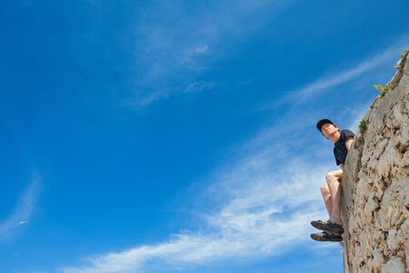 Young man sitting on the edge of stone wall and looking in  the distance. Stock Photo - 27467410