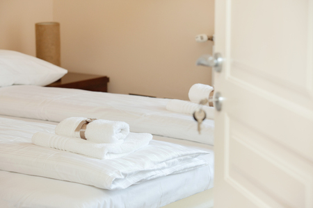 White towels with brown ribbon folded on white sheets in a hotel room