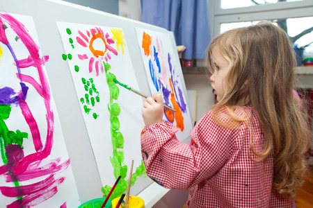 Cute little blond girl holding the brush and painting on the paper photo