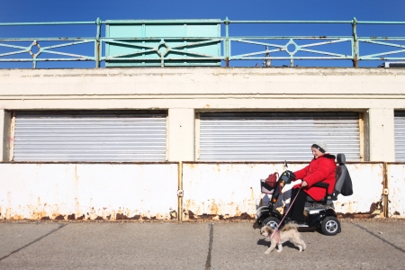 BRIGHTON, UNITED KINGDOM - FEB 2: Disabled woman in electric wheel chair with her dog on February 2, 2011 in Brighton, United Kingdom. Brighton seafront has access ramps for disabled people in wheel chairs.