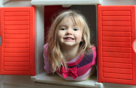 Little blond girl smiling through the window of kids playhouse photo