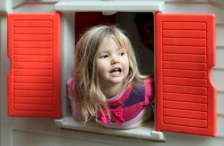 Little blond girl looking through the window of kids playhouse photo