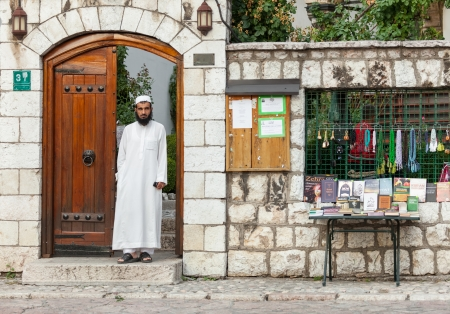 sunni: SARAJEVO, BOSNIA AND HERZEGOVINA - AUGUST 13, 2012: Religious Muslim man stands in doorway on street close to main mosque in old town Sarajevo.