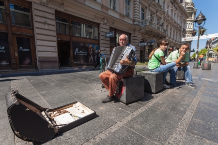 BELGRADE, SERBIA - AUG 15: Old man playing accordion on the street on August 15, 2012 in Belgrade, Serbia. City is famous for having Festival of street performers.