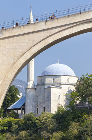 MOSTAR, BOSNIA AND HERZEGOVINA - AUGUST 10, 2012: Tourists on the Old Bridge with mosque in the background. Bridge is a UNESCO World Heritage Site.