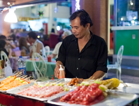 BANGKOK, THAILAND - JANUARY 9, 2012: Man prepares traditional Thai food on Khao San Road food stall. Everyday thousands of tourists and locals buys food on these stalls.