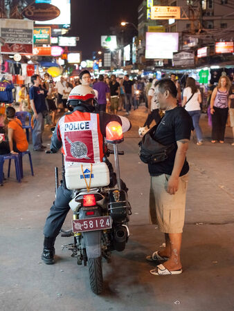 sniffer: BANGKOK, THAILAND - JANUARY 9, 2012: Local man talks on the street with policeman on the motorcycle on Khao San Road. Royal Thai Police counts about 230,000 officers.