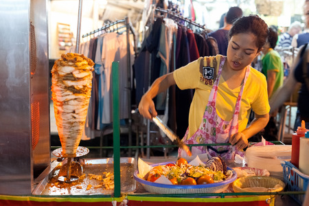 BANGKOK, THAILAND - JANUARY 9, 2012: Woman prepares traditional Thai food on Khao San Road food stall. Everyday thousands of tourists and locals buys food on these stalls.