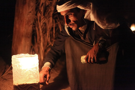 DAHAB, EGYPT - JANUARY 24, 2011: Bedouin sits by the light at night. Bedouin culture still survives in the Sinai, where there is a growing appreciation of its value and its fragility.