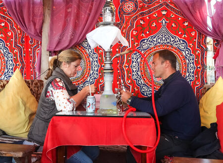 DAHAB, EGYPT - JANUARY 24, 2011: Couple sitting in the oriental bar with nargile on the table. These water-pipes allow you to smoke flavoured tobacco as it is bubbled through water.