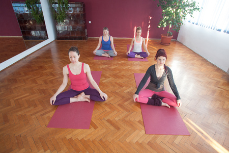 Group of young women practicing yoga at yoga centre. photo