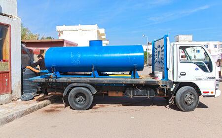 cisterna: Dahab, Egipto - el 28 de enero 2011: cisterna azul y trabajador verter el agua dulce de la cisterna al barril. Editorial