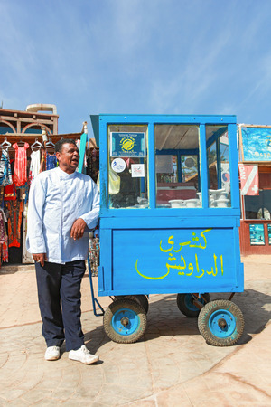ambulant: DAHAB, EGYPT - JANUARY 29, 2011: Vendor on the street next to stand. Street food is the cheapest way for tourists to get a meal.