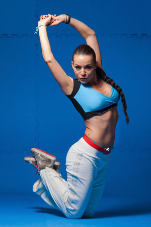 Young dancer in movement on blue background photo