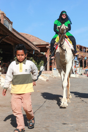 rely: DAHAB, EGYPT - JANUARY 30, 2011: Young local boy leading female tourist on a camel. Local bedouins rely on tourism to make a living in the harsh desert.