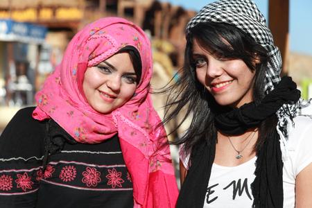 arab hijab: DAHAB, EGYPT - JANUARY 30, 2011: Portrait of modern young Egyptian girls woman wearing hijab, traditional head cover or wrap worn by Muslim women.
