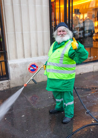 collectors: PARIS, FRANCE - JANUARY 4, 2012: Elderly worker washes street with mini wash. Paris is one of the very few cities in the world with a dual water system. Editorial
