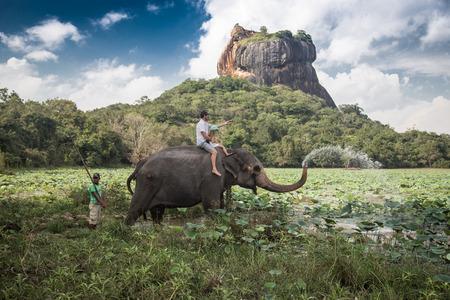 SIGIRIYA, SRI LANKA - 28 FEBRUARY 2014  Man and child riding on the back of elephant with rock of Sigiriya as backdrop and mahout standing at rear