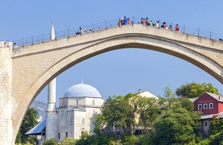 souvenir traditional: MOSTAR, BOSNIA AND HERZEGOVINA - AUGUST 10, 2012: Tourists on the Old Bridge with mosque in the background. Bridge is a UNESCO World Heritage Site.