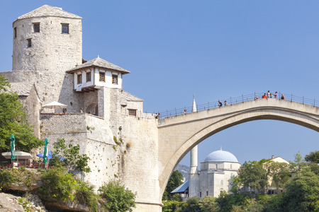 heritage site: MOSTAR, BOSNIA AND HERZEGOVINA - AUGUST 10, 2012: Tourists on the Old Bridge with mosque in the background. Bridge is a UNESCO World Heritage Site.