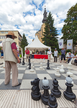 SARAJEVO, BOSNIA AND HERZEGOVINA - AUG 11: People play chess on the street with large chess pieces on August 11, 2012 in Sarajevo, B&H. It is very popular place for older people in Sarajevo.
