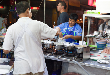 BANGKOK, THAILAND - JANUARY 9, 2012: Man prepares traditional Thai food on a street food stall. Everyday thousands of tourists and locals buys food on these stalls.
